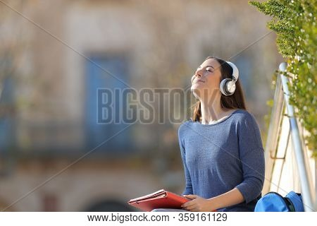 Student Meditating Listening To Music Wearing Headphones Sitting Outdoors In A University Campus