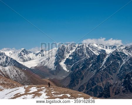 Hiker With A Backpack In The High Snowy Mountains. Great Views Of The Mountain Peaks And The Glacier