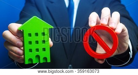 Man Holds A Green House And Red Prohibition Symbol No. Prohibition Of Operation. Denial Of Insurance