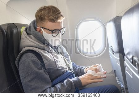 Serious Guy, Young Man On Airplane, Plane In Glasses And Medical Protective Sterile Mask On His Face