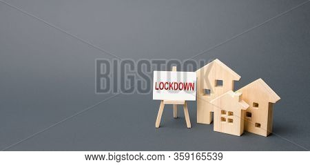 Figures Of Houses And An Easel With The Word Lockdown. Tough Measures To Stop New Infections Of Coro