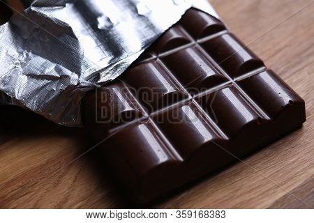 Close-up Of Dark Chocolate Bar In Foil With Open Cover Laying On Wooden Table. Unpacked Sweets With