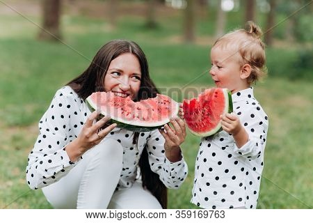 Happy Mother And Daughter Eat Watermelon In Summer Park. Happy Smiling Family Eating Watermelon In P