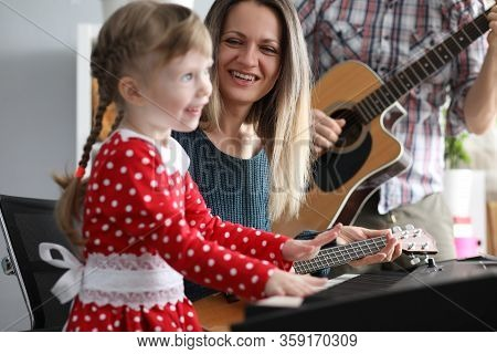 Parents Play Guitars, Daughter On Synthesizer. While Playing Music, Child Develops Mathematical Abil