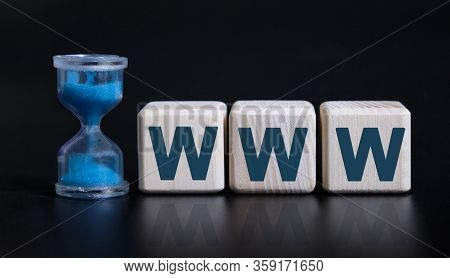 Www - World Wide Web - Concept With An Hourglass. Wooden Cubes On A Black Table