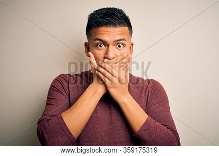 Young handsome latin man wearing casual sweater standing over isolated white background shocked covering mouth with hands for mistake. Secret concept.