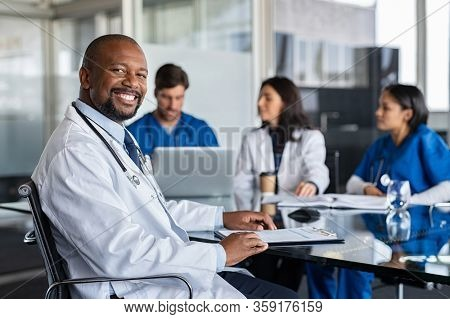 Portrait of successful mature doctor looking at camera with working clinicians behind. Smiling african clinic worker in labcoat and stethoscope sitting in conference room with copy space in hospital.