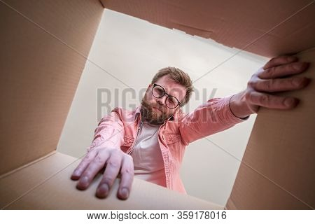 Man With Glasses Looks Into An Unpacked Delivered Box With A Package With Displeasure And Disappoint