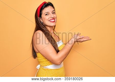 Young hispanic pin up woman wearing fashion sexy 50s style over yellow background pointing aside with hands open palms showing copy space, presenting advertisement smiling excited happy