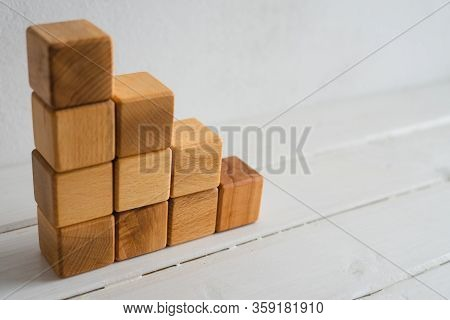 Natural Wooden Cubes Are Built By A Ladder. Cubes On A White Background. World Crisis, Financial Cri