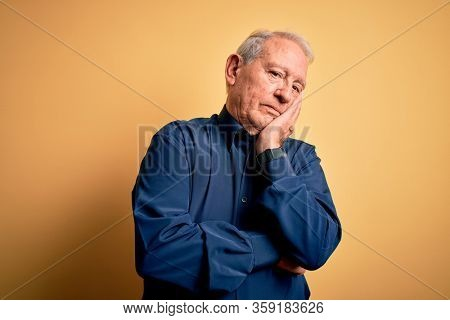 Grey haired senior man wearing casual blue shirt standing over yellow background thinking looking tired and bored with depression problems with crossed arms.