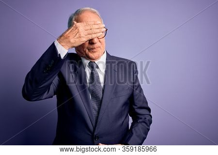 Grey haired senior business man wearing glasses and elegant suit and tie over purple background covering eyes with hand, looking serious and sad. Sightless, hiding and rejection concept