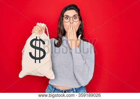 Young beautiful girl holding money bag with dollar symbol for business wealth over red background cover mouth with hand shocked with shame for mistake, expression of fear, scared in silence, secret