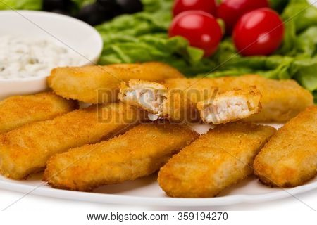 Appetizing fried fish fingers with vegetables. Isolated on white.