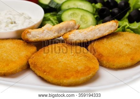 Grilled fish cutlet with vegetables. Isolated on white.