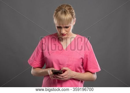 Portrait Of Young Attractive Female Nurse Texting On Smartphone