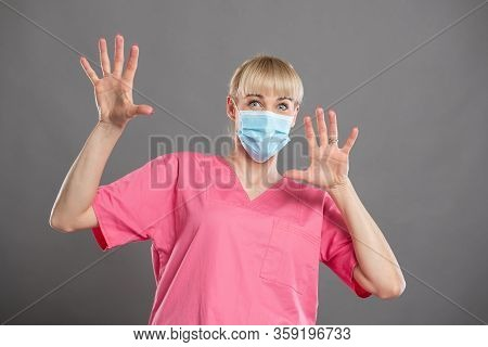 Portrait Of Attractive Female Nurse Wearing Face Mask Looking Scared