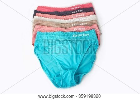 Seven Colorful Panties With Embroidered Days Of The Week On Waistband Isolated On White
