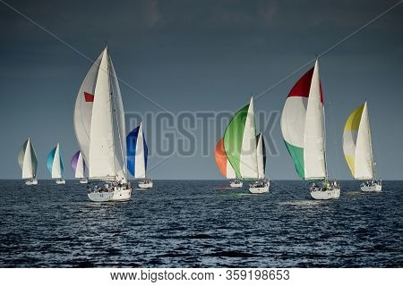 Sailboats Compete In A Sailing Regatta At Sunset, Sailing Race, Reflection Of Sails On Water, Multi-