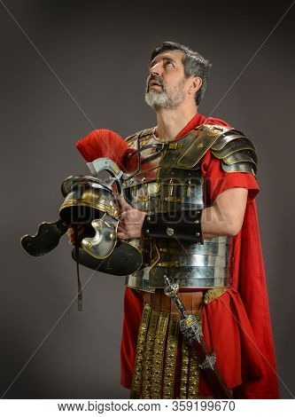Roman soldier looking up and holding his helmet