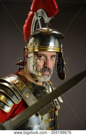 Portrait of a roman soldier holding his sword isolated on a gray background