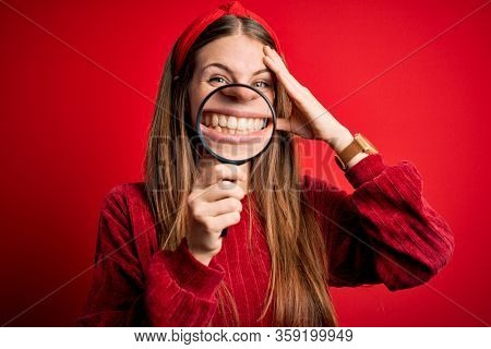 Young beautiful redhead detective woman using magnifying glass over isolated red background stressed with hand on head, shocked with shame and surprise face, angry and frustrated. Fear and upset