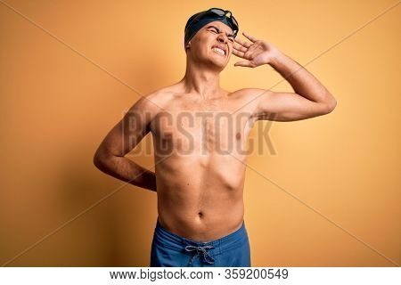 Young handsome man shirtless wearing swimsuit and swim cap over isolated yellow background Suffering of neck ache injury, touching neck with hand, muscular pain