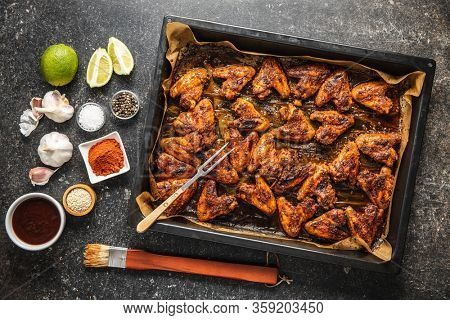Grilled chicken wings in barbecue sauce in baking tray and ingredients. Top view.