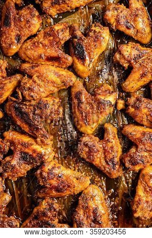 Grilled chicken wings in barbecue sauce on baking paper. Top view.