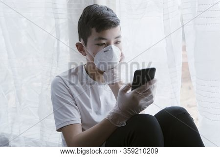 A Concept Photo Of A Teen Boy With A Mask, Gloves,  And A Cell Phone Showing The Boredom Of Staying