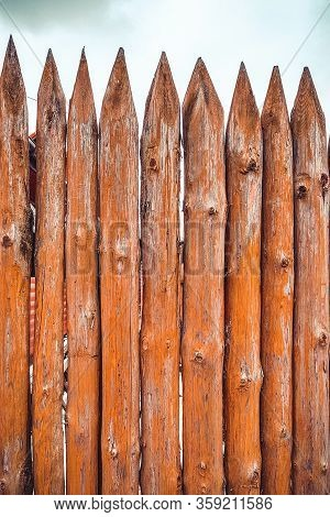 Sharp Peaks On A Wooden Fence. Texture Of Wooden Trunks.