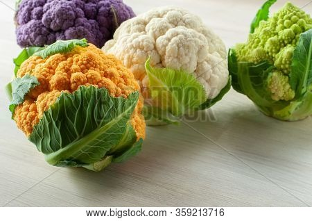 White, Green, Purple And Orange Cauliflowers Lying On A Wooden Table