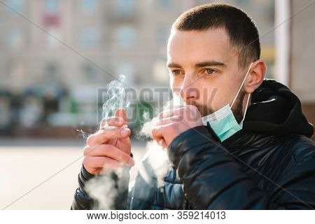 Smoking. Closeup Man With Mask During Covid-19 Pandemic Coughing And Smoking A Cigarette At The Stre