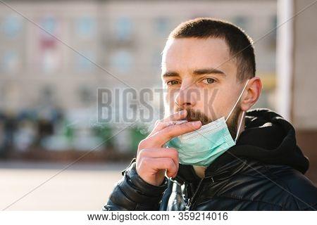 Coronavirus. Smoking. Closeup Man With Mask During Covid-19 Pandemic Smoking A Cigarette At The Stre
