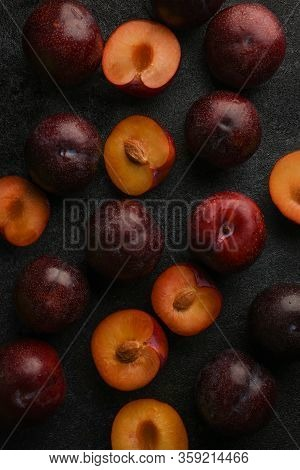 Plums. Fresh Plum. Whole And Halves Of Blue Ripe Plums On A Dark Textured Background. Natural Fruit