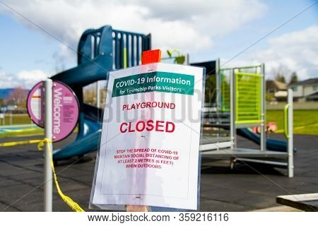 A Covid-19 Warning Sign In Front Of A Toddler Playground
