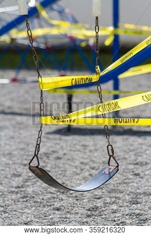 A Single School Yard Swing Is Caution Taped Off Due To Covid-19 Outbreak.