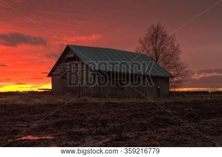The Sun Sets Beautifully On A Spring Night At The Northern Finland. The Old Barn House Stands By A B
