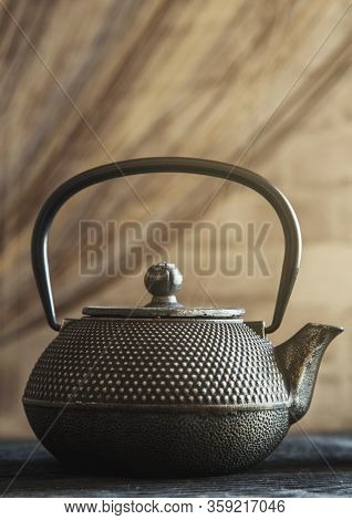 Close Up Black Metall Tea Pot On A Wooden Background Toning Photo