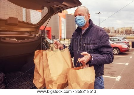 A Man With A Protective Mask On His Face Loads Food Packages Into The Car. Food Delivery. Coronaviru