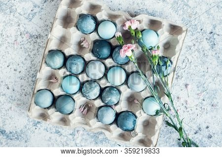 Blue Easter Eggs With Pink Flowers. Easter Composition On Grey Concrete Background. Natural Ecologic
