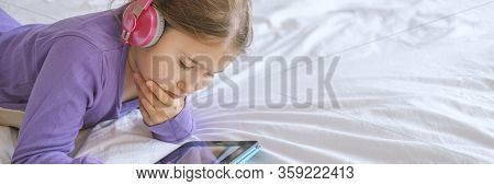 Young Teenager Girl In Pink Headphones With Tablet Device In Home Lying On White Bed. Stock Photo Ba