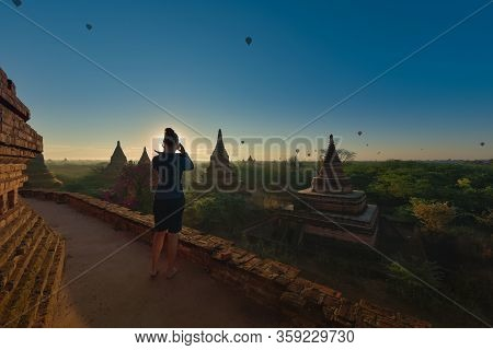 Bagan Myanmar Young Woman Photographs Beautiful Stupas And Hot Air Balloons At Sunrise
