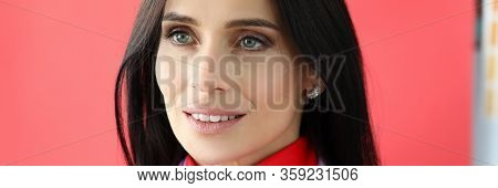 Close-up View Of Attractive Female With Mysterious Glance And Light Smile Standing On Red Background