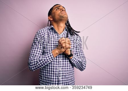 Young handsome african american afro man with dreadlocks wearing casual shirt begging and praying with hands together with hope expression on face very emotional and worried. Begging.