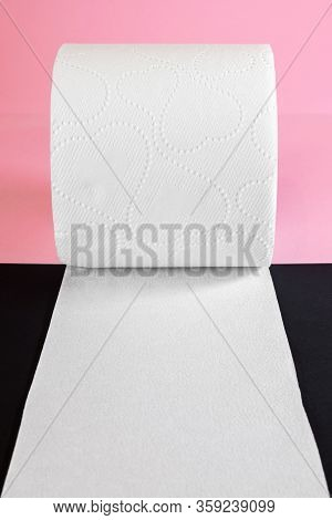 Unwrapped White Toilet Paper Roll On Black And Pink Background With Copy Space