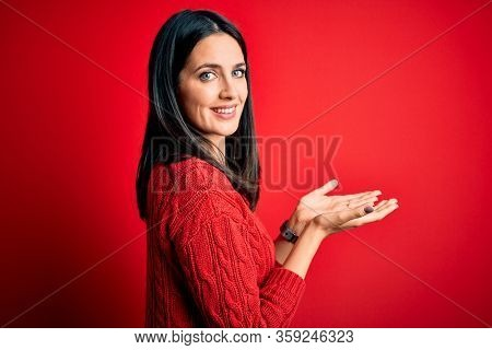 Young brunette woman with blue eyes wearing casual sweater over isolated red background pointing aside with hands open palms showing copy space, presenting advertisement smiling excited happy