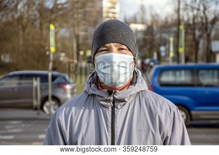 Street Portrait Of A Man Of 30-35 Years Of Eastern Appearance In A Medical Mask, Past Which People A