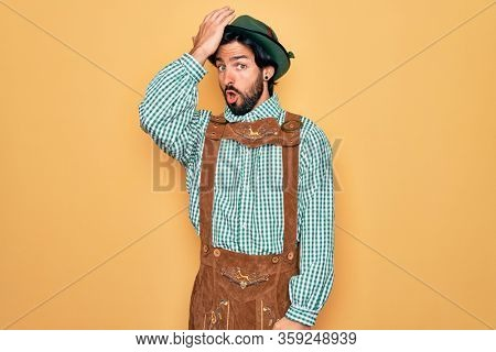Young handsome man wearing tratidional german octoberfest custome for Germany festival surprised with hand on head for mistake, remember error. Forgot, bad memory concept.