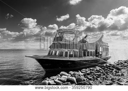 Black And White Shabby Aged Boat Floating In Sea Water Near Rocky Coast Against Cloudy Sky